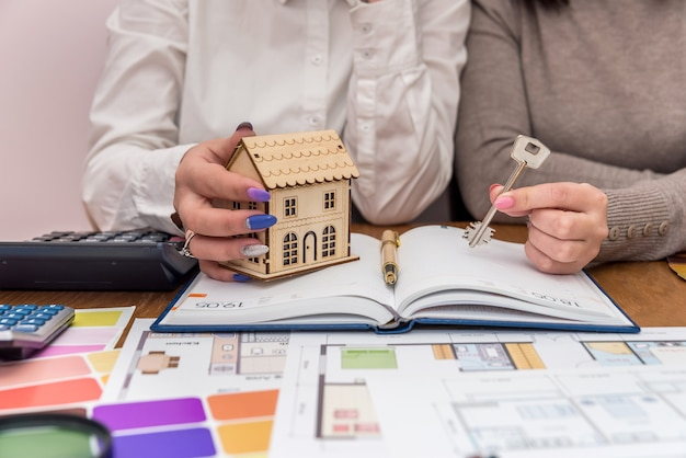 Mãos femininas com modelo e chave de casa de madeira