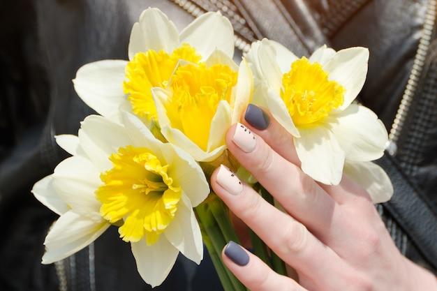 Mãos femininas com narcisos, manicure. fechar-se