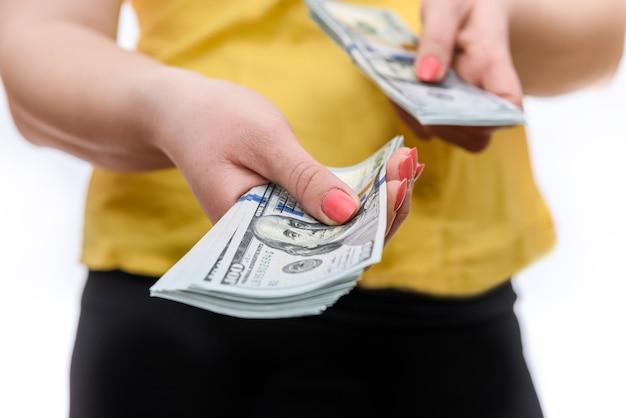 Mãos femininas com notas de dólar americano fecham
