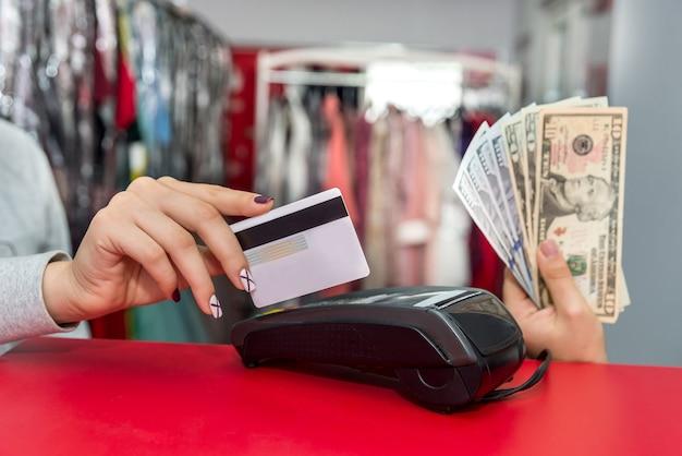Mãos femininas com notas de dólar e cartão de crédito