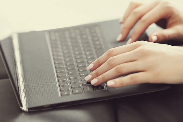 Mãos femininas com os dedos sobre o teclado do laptop