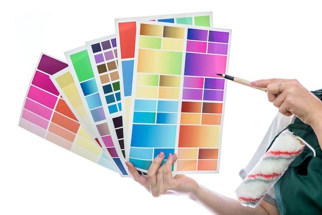 Mãos femininas com paleta de cores isolada na parede branca