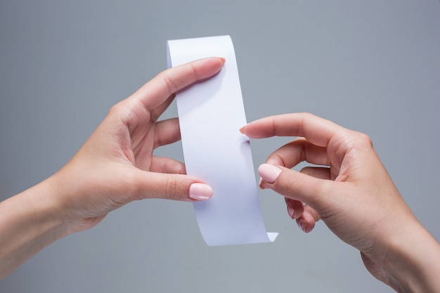 Mãos femininas com papel de transação vazio ou cheque de papel em fundo cinza