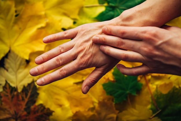 Mãos femininas com pele envelhecida e folhas de outono