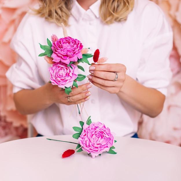 Mãos femininas com peônias artesanais