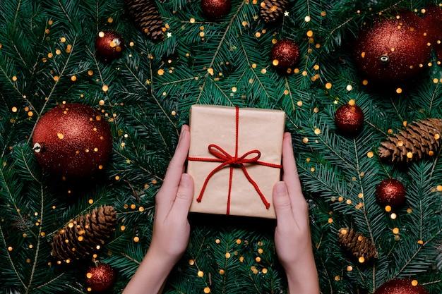 Mãos femininas com presentes e decorações de natal