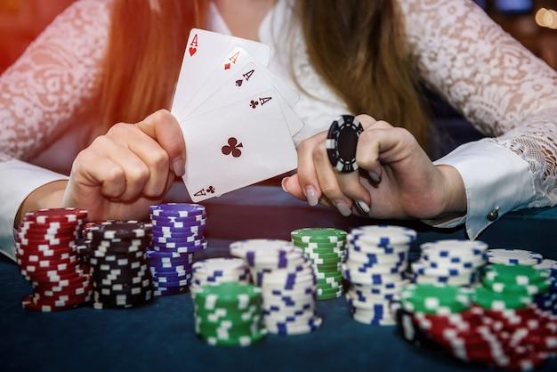 Mãos femininas com quatro ases e fichas de pôquer