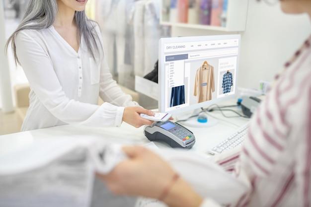 Mãos femininas com smartphone sobre o terminal pos no balcão perto da tela do computador e do vendedor