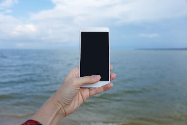 Mãos femininas com smartphone tirando fotos do mar
