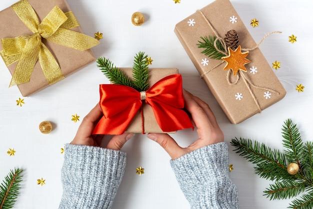 Mãos femininas com suéter de lã segurando um presente em estilo vintage perto de dois presentes em papel ecológico