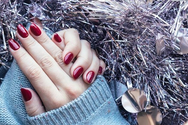 Mãos femininas com suéter tricotado com unhas bordô brilhantes no fundo de enfeites de natal prateados