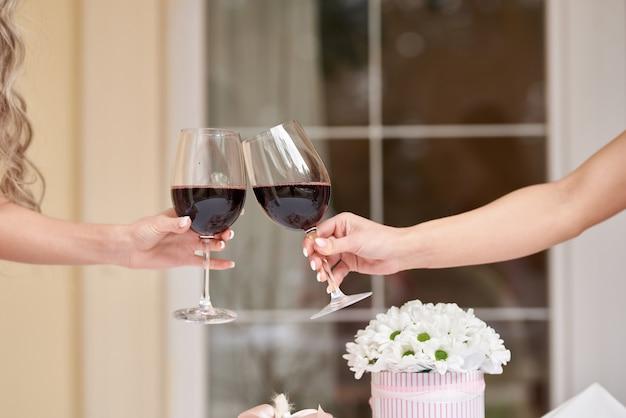 Mãos femininas com taças de vinho tinto