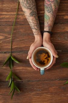 Mãos femininas com tatuagens segurando uma xícara de chá perfumado