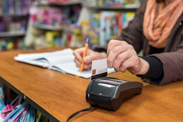 Mãos femininas com terminal e cartão de crédito