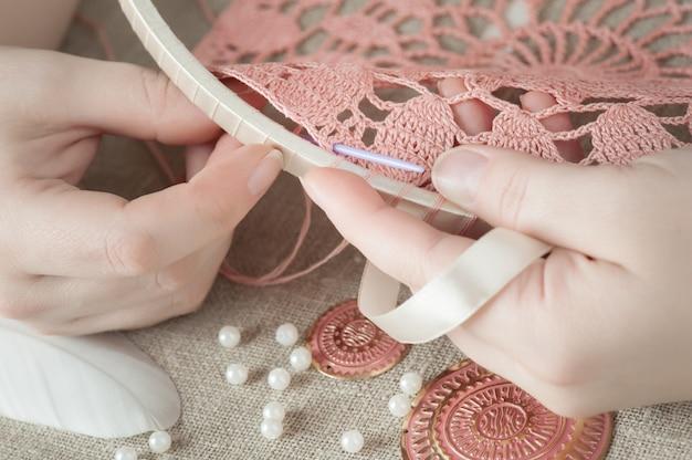 Mãos femininas com tricô rosa