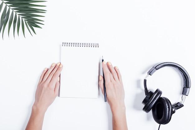 Mãos femininas com um caderno e lápis, fones de ouvido e planta na mesa branca