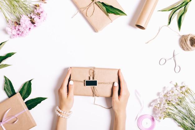 Mãos femininas com um manicure segurar uma caixa com um presente e fita em uma mesa branca.