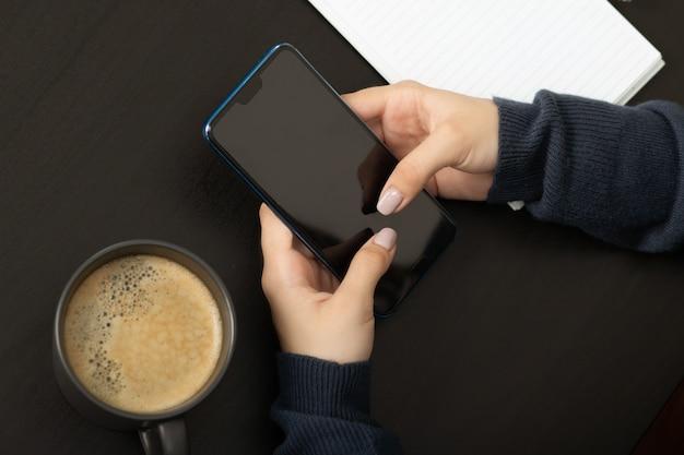 Mãos femininas com um smartphone em uma mesa em um café se comunicando nas redes sociais