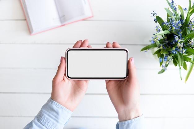 Mãos femininas com um smartphone. tela em branco branca. mesa com flores e caderno