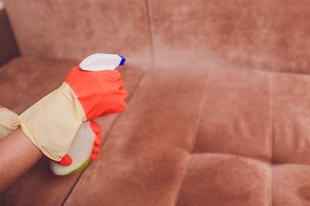 Mãos femininas com um sofá de limpeza de spray