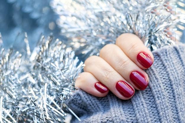 Mãos femininas com um suéter de malha cinza com manicure brilhante