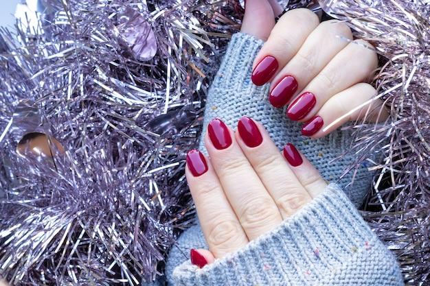 Mãos femininas com um suéter de malha com unhas bordô em enfeites de natal