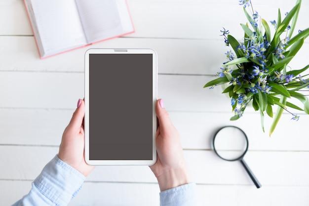 Mãos femininas com um tablet. tela em branco preta. mesa com flores e caderno