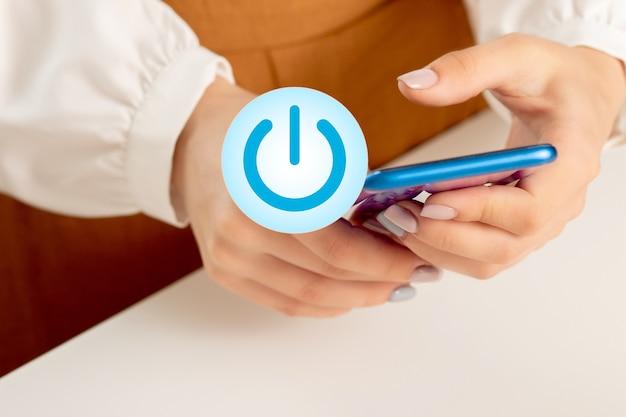 Mãos femininas com um telefone celular e o botão do ícone de energia. o conceito de tecnologia inicial