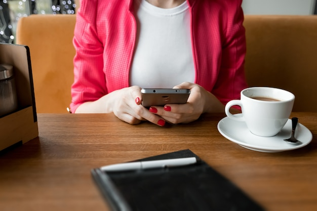 Mãos femininas com um telefone preto, uma xícara de café