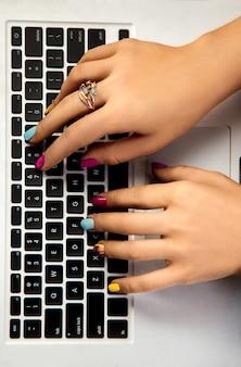 Mãos femininas com uma bela manicure digitando em um laptop. trabalhador