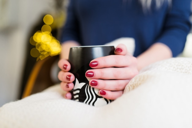 Mãos femininas com uma bela manicure segurar uma xícara de café