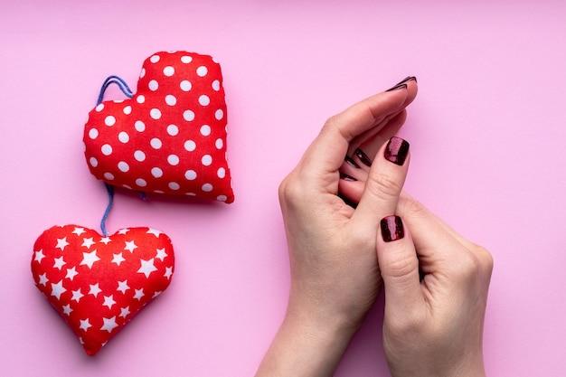 Mãos femininas com uma bela manicure - unhas com brilho vermelho escuro em fundo rosa com dois corações vermelhos suaves