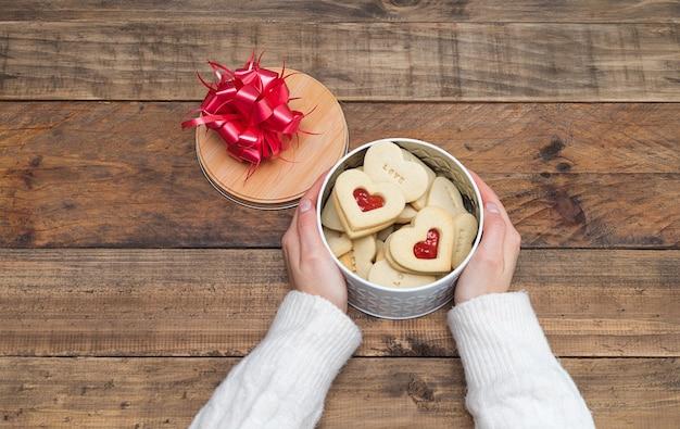Mãos femininas com uma caixa aberta de biscoitos em forma de coração sobre uma base de madeira. dia dos namorados conceito, dia das mães, aniversário.