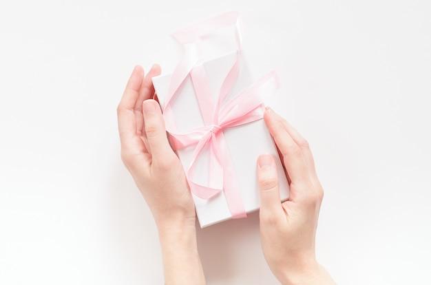 Mãos femininas com uma caixa de presente com uma fita rosa.