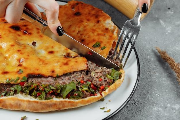 Mãos femininas com uma faca e um garfo cortam khachapuri com cordeiro e pimenta