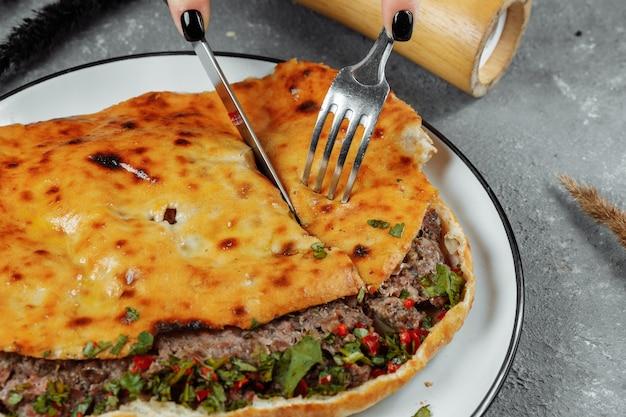 Mãos femininas com uma faca e um garfo cortaram khachapuri com cordeiro e pimenta. comida nacional da geórgia.