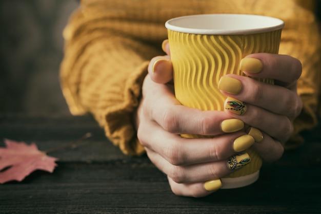 Mãos femininas com uma manicure brilhante e um copo de papel amarelo. fechar-se