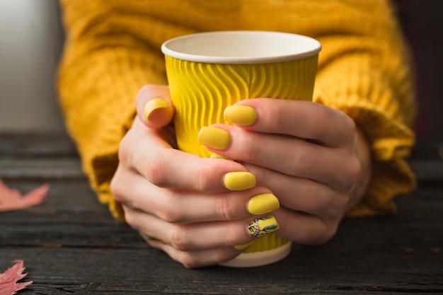 Mãos femininas com uma manicure brilhante e um copo de papel amarelo