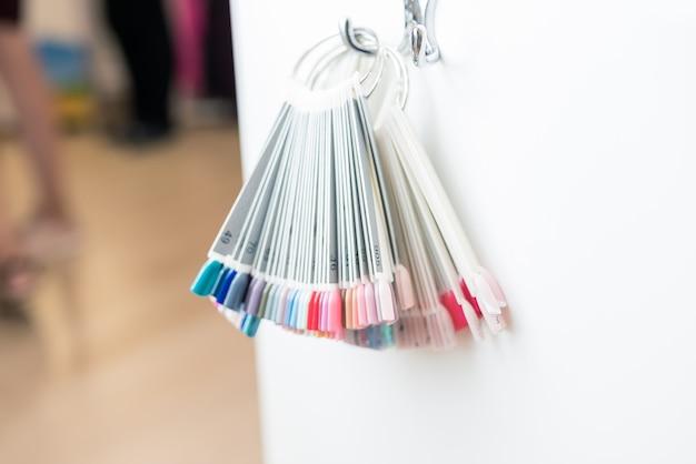 Mãos femininas com uma manicure perfeita e amostras de design de unhas. salão de beleza para unhas. verniz para as unhas em cores diferentes. esmalte colorido