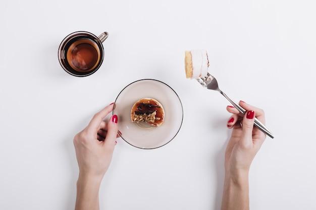 Mãos femininas com uma manicure vermelha fixada em um pedaço de bolo de garfo