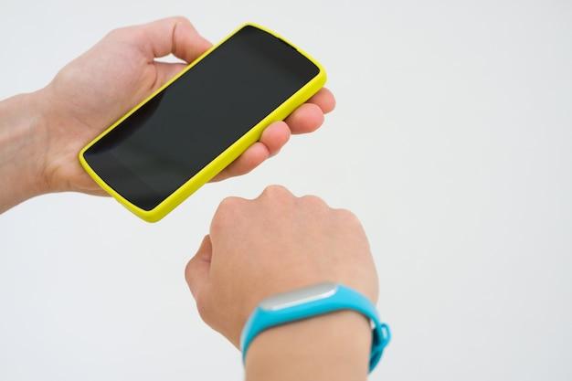Mãos femininas com uma pulseira de esportes e telefone inteligente close-up em um fundo branco