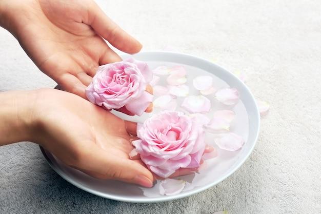 Mãos femininas com uma tigela de água de spa aroma na mesa, closeup