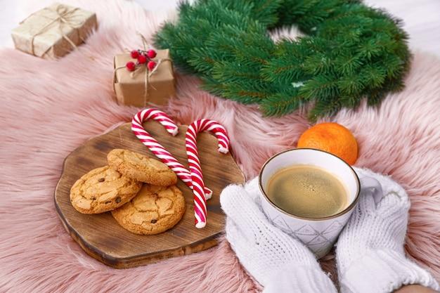 Mãos femininas com uma xícara de café, biscoitos e uma decoração de natal em xadrez macio