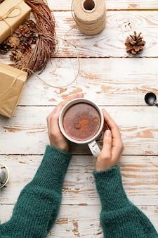 Mãos femininas com uma xícara de chocolate quente na mesa de madeira