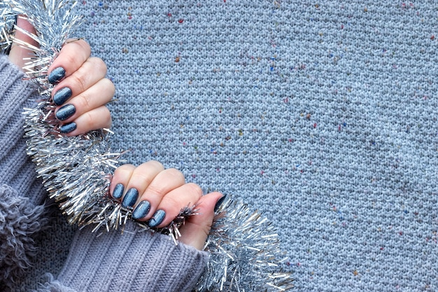 Mãos femininas com unhas brilhantes de azul cinza escuro em fundo de malha com enfeites de natal prata