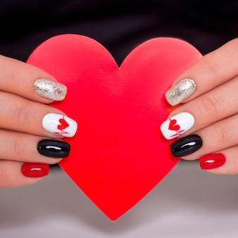 Mãos femininas com unhas de manicure da moda, desenho de corações