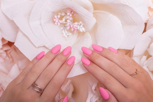 Mãos femininas com unhas de manicure de casamento esmalte de gel rosa