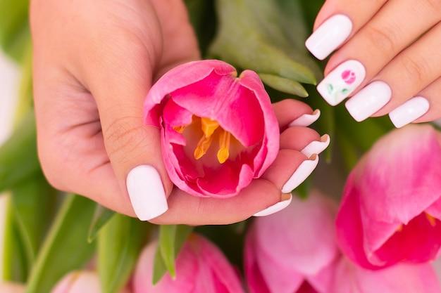 Mãos femininas com unhas de manicure de primavera