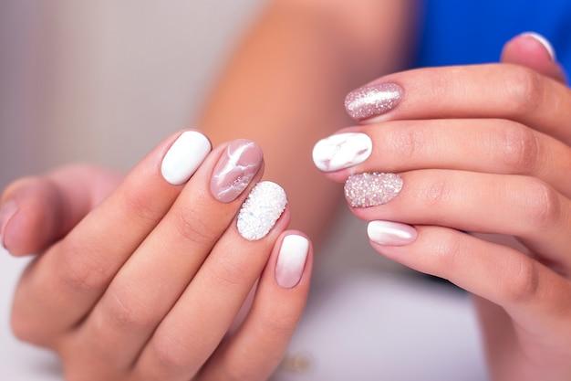 Mãos femininas com unhas de manicure luxuosas e polis de gel rosa e branca