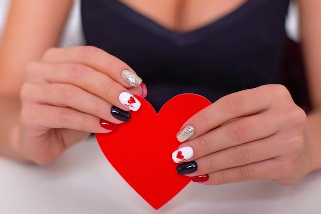 Mãos femininas com unhas de manicure românticas, desenho de corações